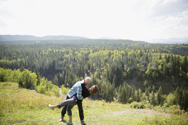 Playful mature couple hiking at sunny remote hilltop - HEROF14051 - Hero Images/Westend61