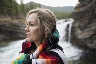 Pensive blonde woman wrapped in blanket looking away near waterfall - HEROF14060