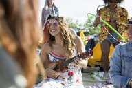 Young woman playing ukulele at summer music festival campsite - HEROF14063