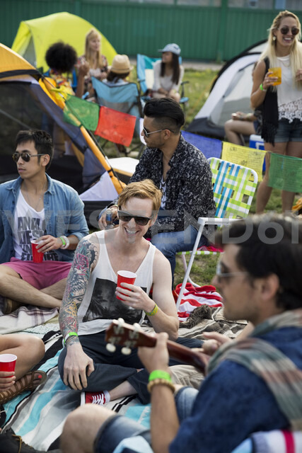 Young friends hanging out at summer music festival campsite - HEROF14069 - Hero Images/Westend61