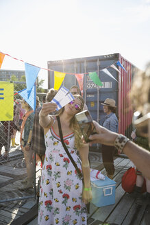 Young woman with summer music festival tickets posing for photograph outside entrance - HEROF14081