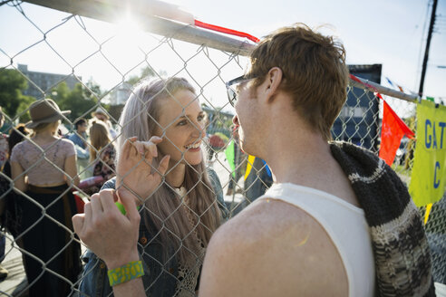 Young couple face to face at summer music festival chainlink fence - HEROF14084