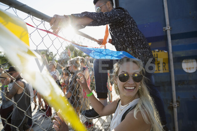 Young man and woman climbing fence at summer music festival - HEROF14087