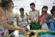 Young friends looking at merchandise in vendor booth at summer music festival - HEROF14096