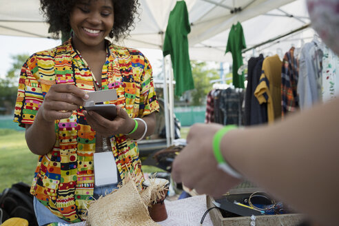 Young woman using credit card reader at vendor booth at summer music festival - HEROF14099