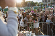 Young women taking selfie in crowd at summer music festival - HEROF14114