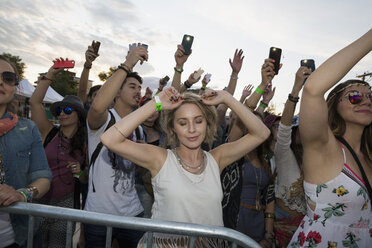 Young woman dancing with eyes closed in crowd at summer music festival - HEROF14117