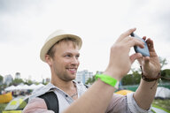 Young man taking selfie at summer music festival campsite - HEROF14120