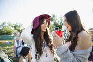 Young women drinking and hanging out at summer music festival campsite - HEROF14126