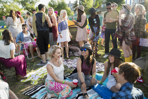 Young friends drinking and hanging out at summer music festival campsite - HEROF14129