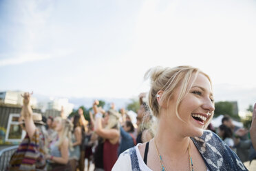 Young woman laughing in crowd at summer music festival - HEROF14144