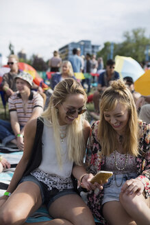 Young women with cell phone at summer music festival campsite - HEROF14150