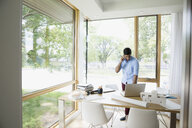 Young man talking on cell phone working in dining room - HEROF14174