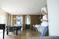 Woman with hair in towel drinking coffee in kitchen - HEROF14180