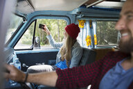 Woman in camper van photographing scenery with camera phone - HEROF14189