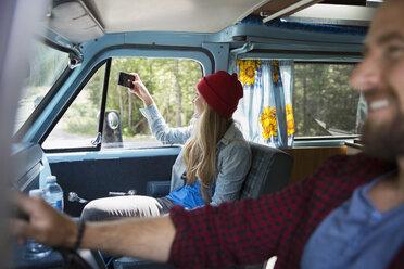 Woman in camper van photographing scenery with camera phone - HEROF14189