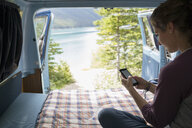 Woman texting with cell phone in back of camper van with remote lake view - HEROF14192