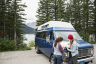 Women viewing map on camper van parked at remote lakeside - HEROF14195