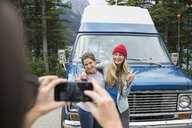 Woman with camera phone photographing friends outside camper van - HEROF14198