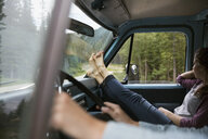 Woman riding with bare feet up in camper van enjoying view of woods - HEROF14201
