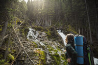 Woman hiking with backpack looking up at waterfall view in woods - HEROF14204