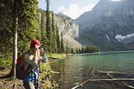 Woman with digital camera photographing remote sunny mountain lake view - HEROF14207