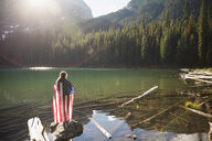 Woman wrapped in American flag on log enjoying sunny remote mountain lake view - HEROF14210