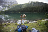 Young female friends hiking wading into remote lake - HEROF14213