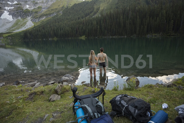Young couple hiking wading into remote lake - HEROF14216