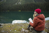 Woman sketching at remote lakeside - HEROF14219