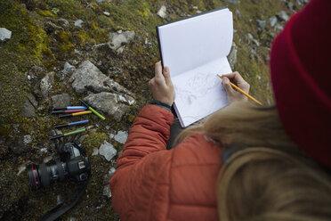 Woman sketching mountain in journal - HEROF14222