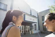 Women friends laughing outside sunny movie theater - HEROF14240