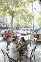Women friends drinking coffee and using digital tablet at urban sidewalk cafe - HEROF14246