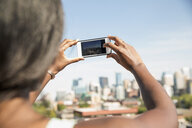 Woman using camera phone photographing sunny cityscape - HEROF14252