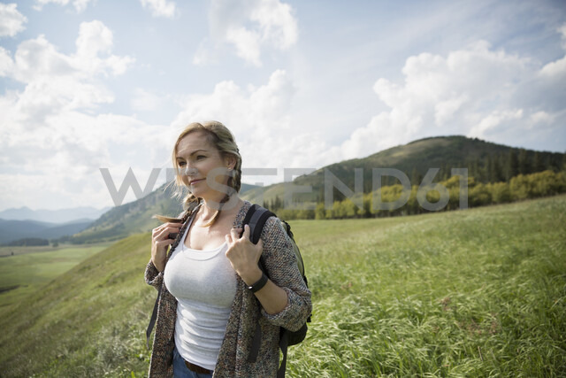 Woman with backpack hiking in remote sunny rural field - HEROF14267 - Hero Images/Westend61