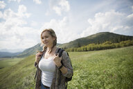 Woman with backpack hiking in remote sunny rural field - HEROF14267