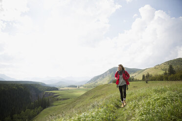 Woman with backpack hiking in remote sunny rural field - HEROF14273