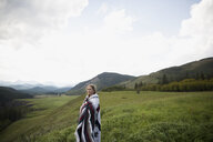 Woman wrapped in blanket in remote rural field - HEROF14276