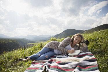 Woman writing in journal on blanket in sunny remote rural field - HEROF14279
