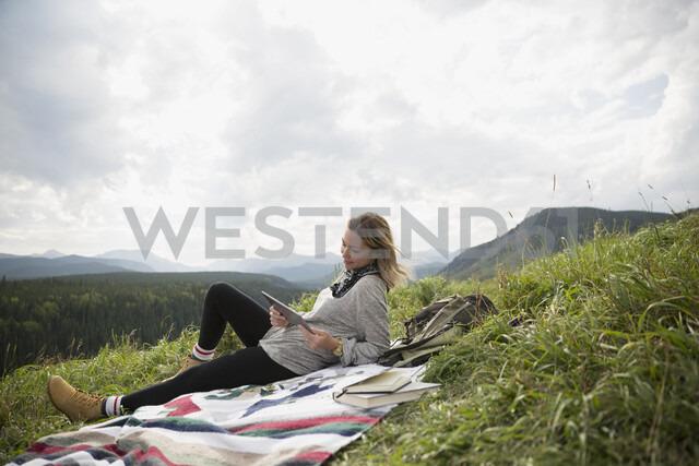 Woman using digital tablet on blanket in remote rural field - HEROF14282 - Hero Images/Westend61