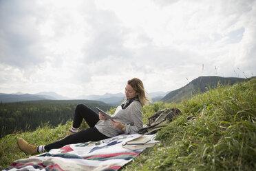 Woman using digital tablet on blanket in remote rural field - HEROF14282