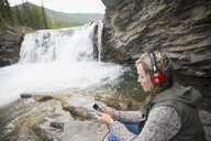 Woman listening to music with headphones and mp3 player at waterfall - HEROF14288