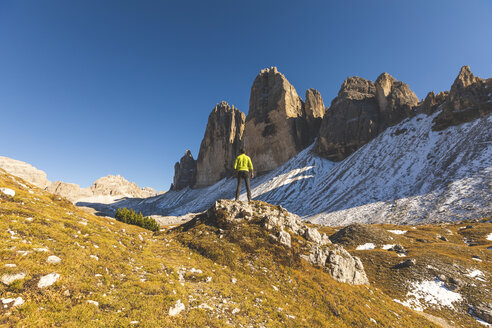 Italy, Tre Cime di Lavaredo, man hiking and standing in front of the majestic three peaks - WPEF01330