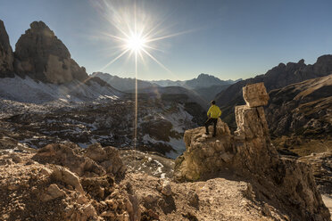 Italy, Tre Cime di Lavaredo, man hiking and looking at the valley with peaks and sun over the horizon - WPEF01333