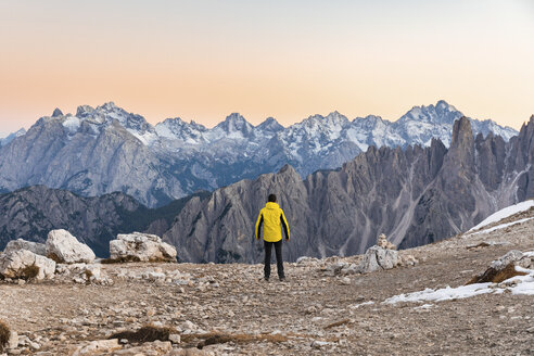 Italy, Tre Cime di Lavaredo, man enjoying colourful mountain peaks at sunset - WPEF01336