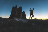 Italy, Tre Cime di Lavaredo, silhouette of a man jumping at the three peaks at dusk - WPEF01339