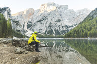 Italy, Braies Lake, man sitting on a rock at the lakeside with mountains and forest in background - WPEF01342