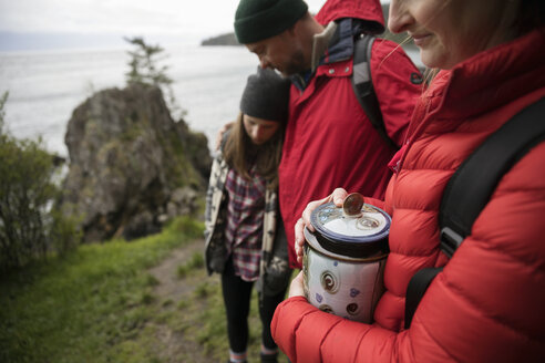 Family with urn spreading ashes on cliff overlooking ocean - HEROF14297