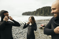 Friends putting on wet suits, preparing for surfing on rugged beach - HEROF14372