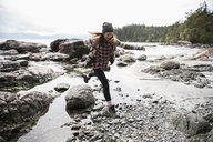 Playful teenage girl jumping over rock on rugged beach - HEROF14423